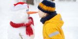 Little Boy Playing With Funny Snowman. Child Reaches For A Snowman's Carrot Nose And Wants To Bite. Active Outdoors Leisure With Children In Winter.